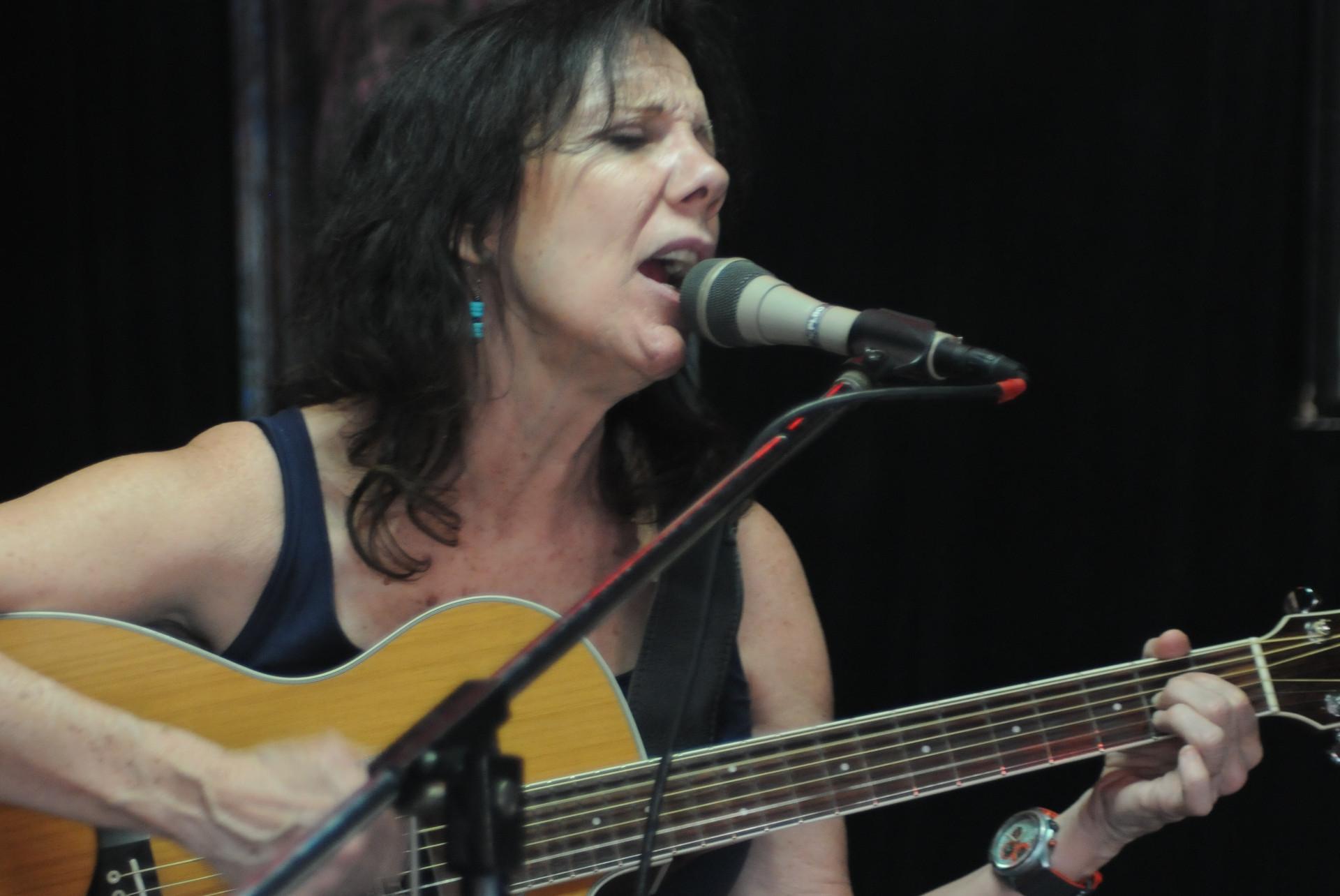 Katrina singing and playing guitar at The Cove
